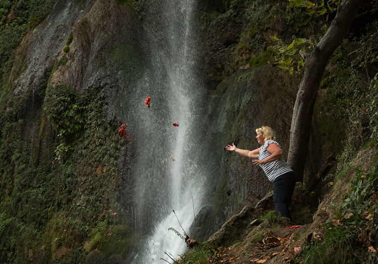 Low Angle View Of Woman Throwing Leaves Against Waterfall In Forest