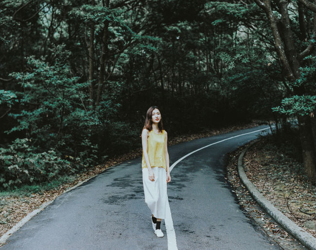 Beautiful Woman Casual Clothing Day Diminishing Perspective Direction Front View Full Length Hairstyle Lifestyles Looking At Camera Nature One Person Outdoors Plant Portrait Real People Road Standing The Way Forward Track Transportation Tree Young Adult Young Women