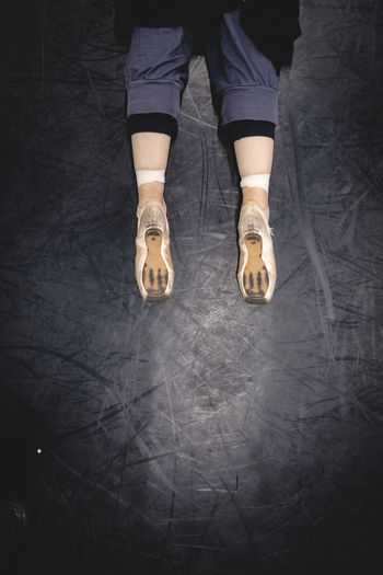 Low Section Of Woman Wearing Ballet Shoes Lying On Floor In Studio