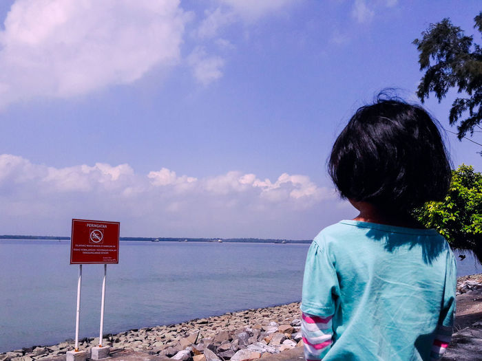 Rear View Of Girl Looking At Sea Against Sky