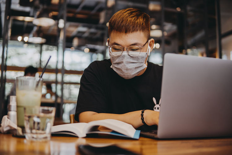 Young man wearing mask using laptop at cafe
