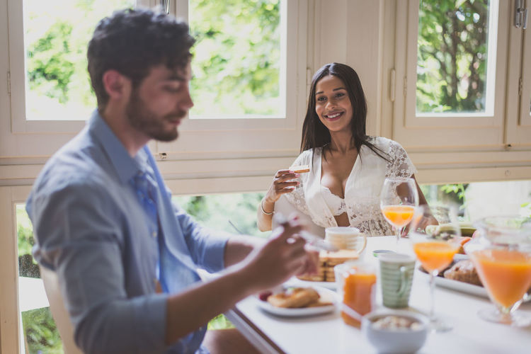 Smiling woman looking at boyfriend while having breakfast at home
