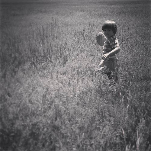 Portrait of boy playing with ball amidst field