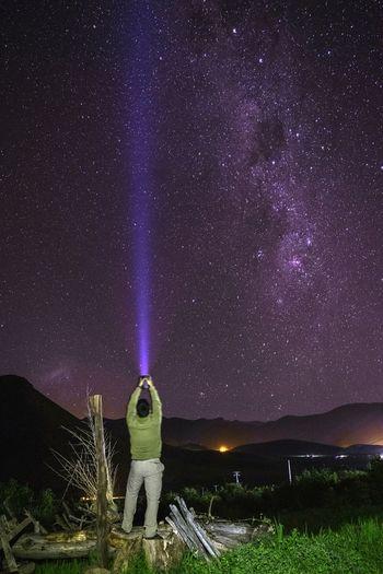 Rear view of man lighting sky with flashlight at night