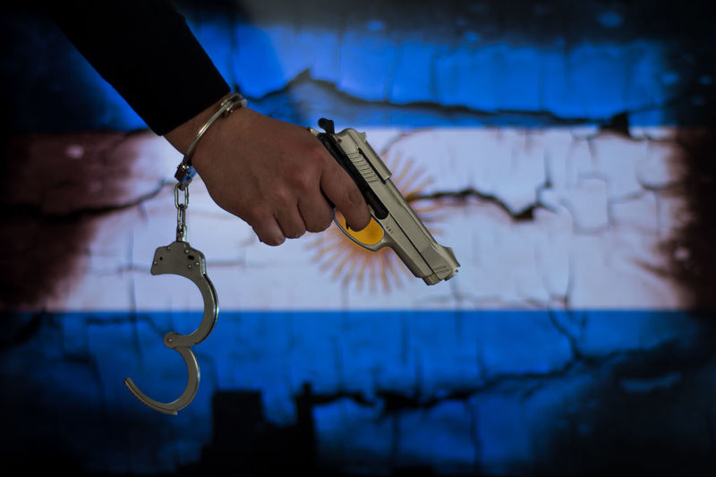 Arjantin Catch Crime Gun Justice - Concept Leakage Murder Arjantina Communication Fishing Hook Flag Focus On Foreground Hand Handcuffs  Handgun Human Body Part Human Hand Justice Law Mafia  Prison Real People Thief Wall - Building Feature