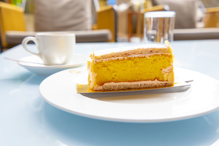 Lemon Cake and Cappuccino Coffee. Glass Of Water Baked Breakfast Cake Cappuccino Close-up Coffee Coffee - Drink Coffee Cup Crockery Cup Dessert Drink Food Food And Drink Freshness Luxury Plate Ready-to-eat Refreshment Slice Of Cake Sweet Sweet Food Table Temptation