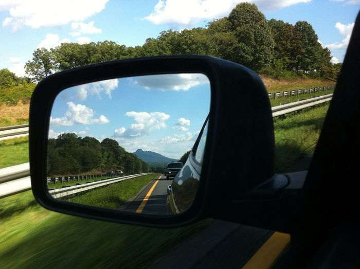 Reflection of clouds in side-view mirror