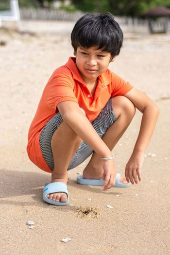 Portrait of boy sitting on sand
