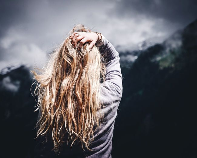Rear View Of Woman With Hand In Hair Against Mountain