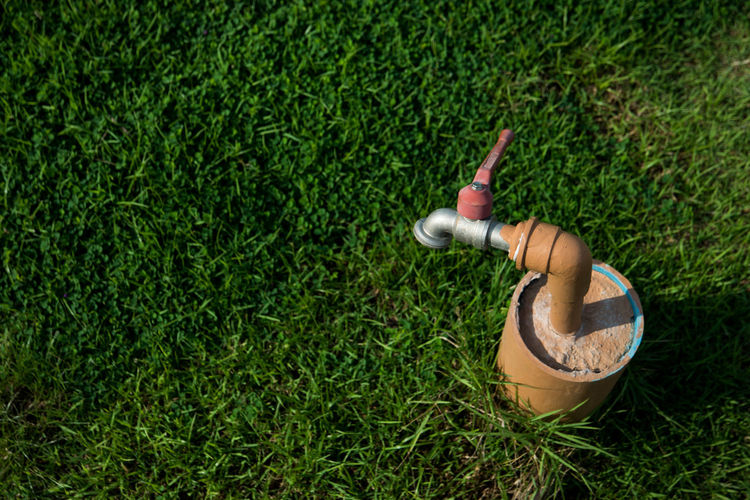 High Angle View Of Faucet On Grassy Field