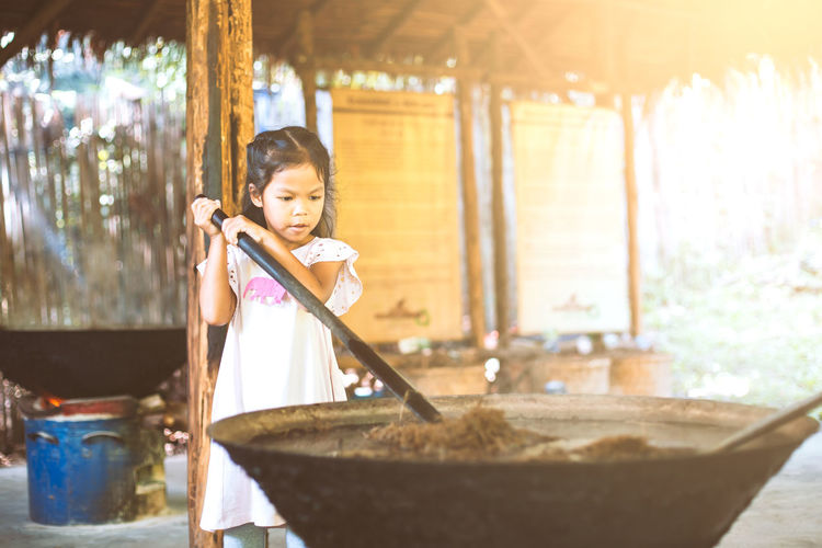 Girl mixing animal dung in container at workshop