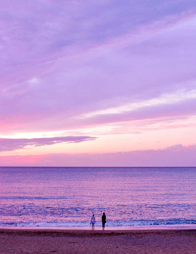 People on beach by sea against sky during sunset