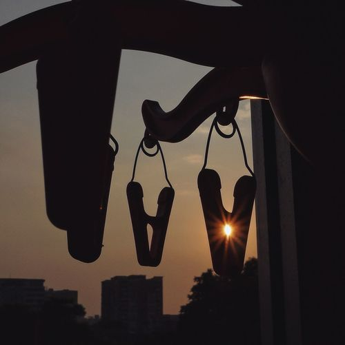 Silhouette Clothespins Hanging From Hooks During Sunset