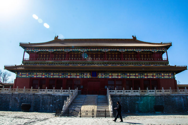 Man walking outside traditional building against clear sky
