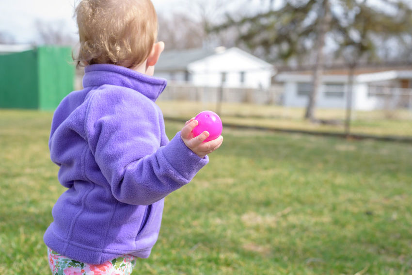 little kids having fun at Easter egg hunt outside Backyard Children Easter Easter Egg Hunt Fun Casual Clothing Child Childhood Day Females Focus On Foreground Grass Holding Innocence Kid Nature One Person Outdoors Pink Color Plastic Easter Eggs Playing Purple Toddler  Warm Clothing Yard