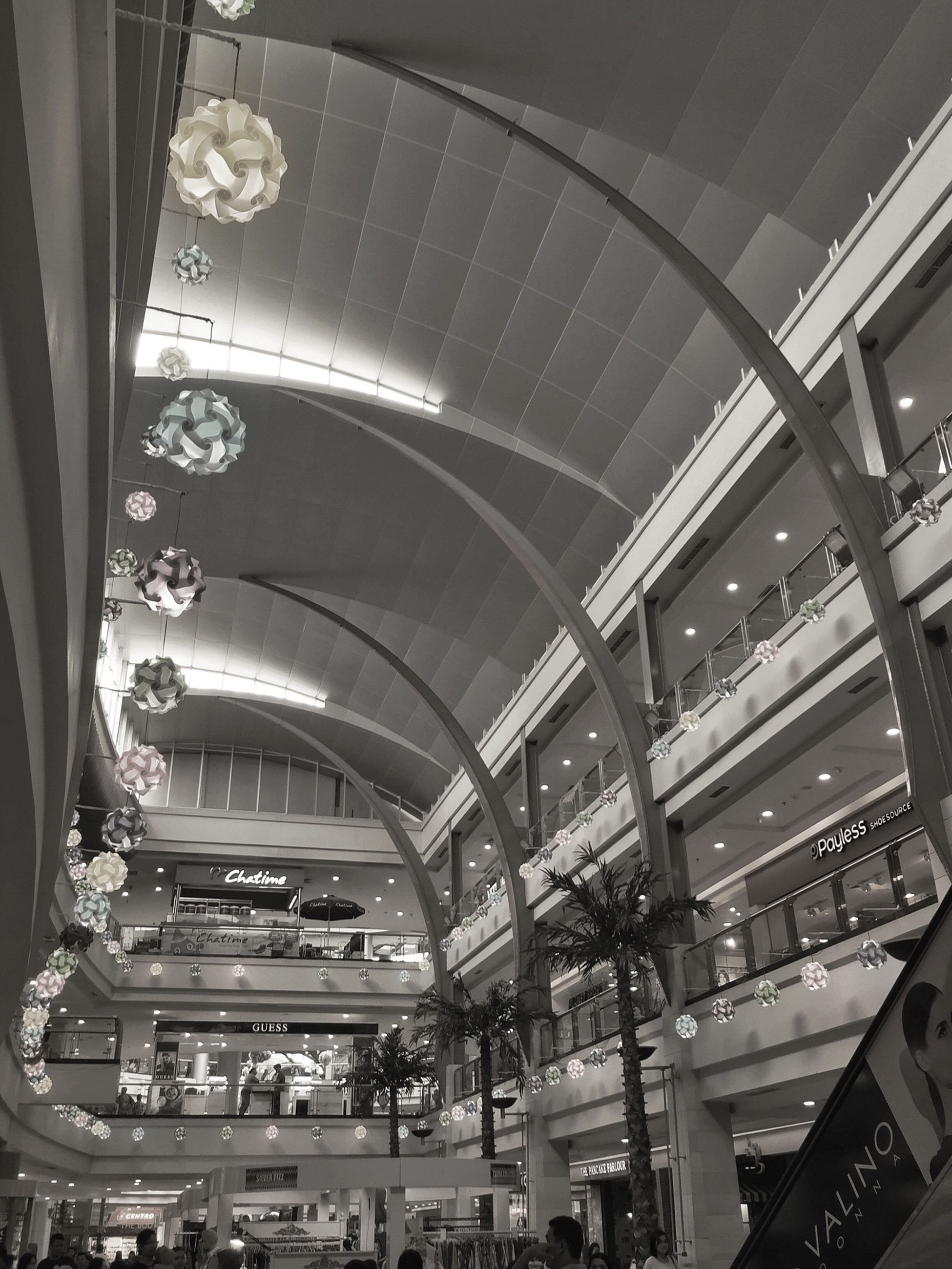 indoors, ceiling, architecture, built structure, illuminated, low angle view, shopping mall, incidental people, interior, lighting equipment, arch, modern, travel, transportation, large group of people, in a row, architectural column, railroad station, architectural feature, high angle view