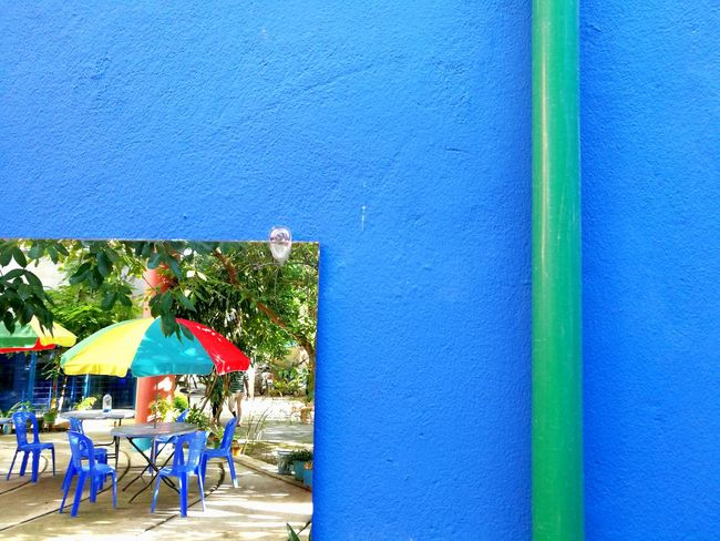 Exploring Style Blue Vibrant Color Outdoors Day Summer TakeoverContrast Colors and patterns Colors Colorful Solid Colors Wall Mirror Reflection Reflections Pipe Contrast Contrasting Colors Blue Wall Umbrella Chair Relaxing Still Life Urban Exploration Tranquility