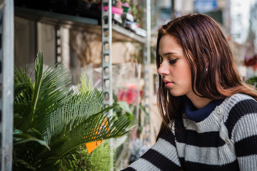 Beautiful brunette woman choosing plants Choice Flower Store Plants Adult Beautiful Woman Close-up Flower Flower Shop Focus On Foreground Headshot Nature One Person One Young Woman Only Outdoors People Plant Real People Young Adult