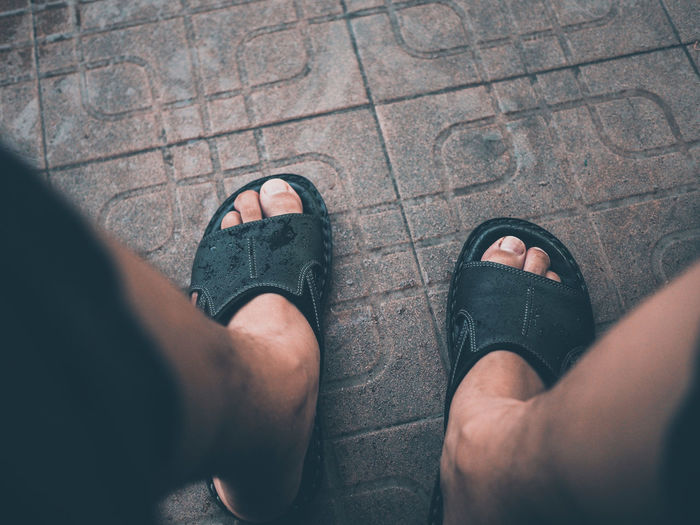 Low Section Of Man Wearing Sandals On Footpath
