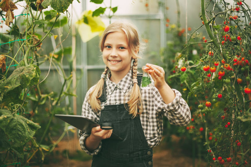 A beautiful little teenage girl with a tablet in her hands examines a sample of a plant through
