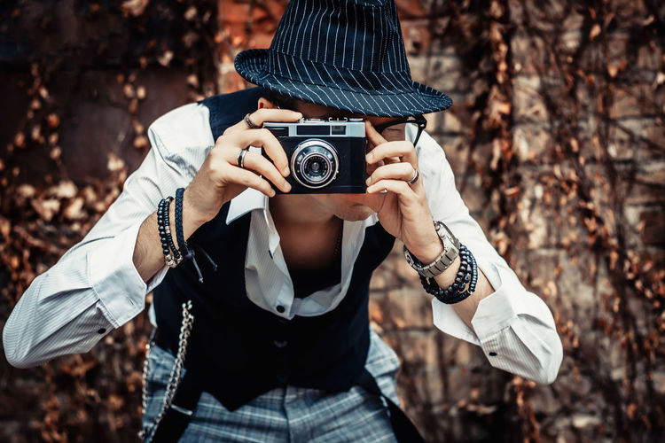 Photographer using retro photo camera while taking picture outdoors.