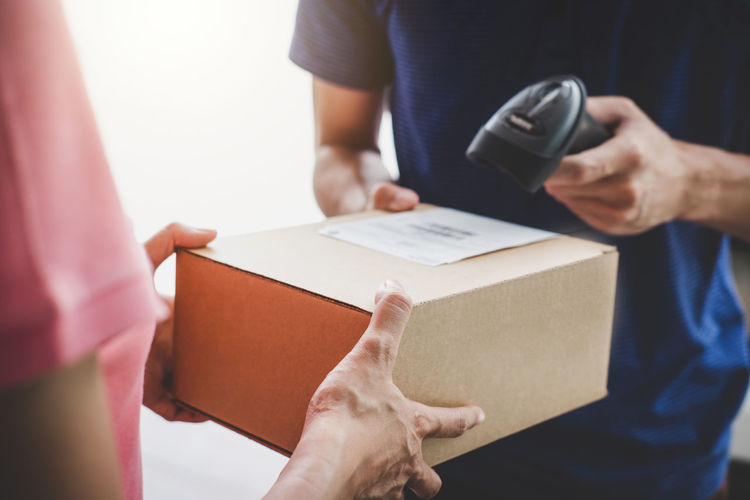 Close-up of businesswoman holding box while man scanning box with barcode scanner