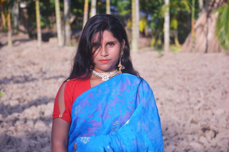 Portrait of girl wearing sari standing against trees