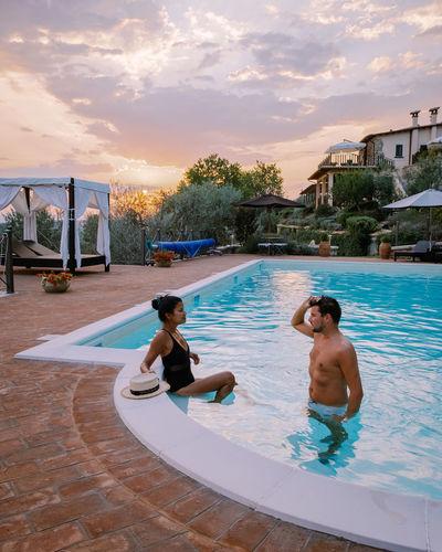 Men in swimming pool against sky