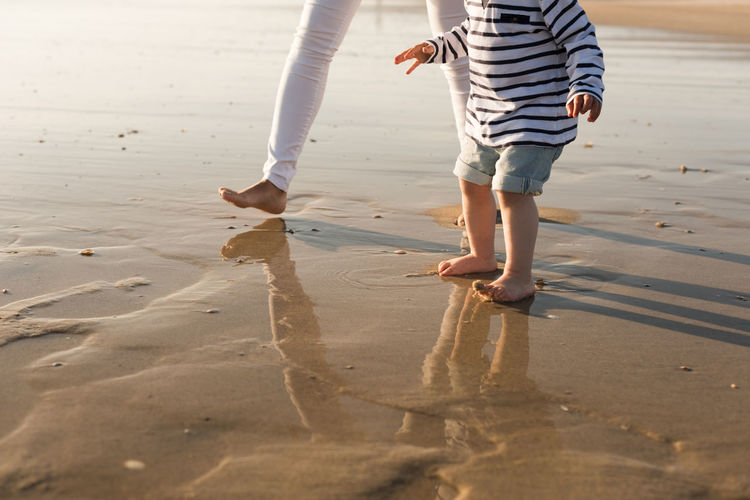 Low Section Of Mother And Son Walking At Beach