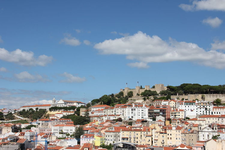 Castelo sao jorge and residential district against blue sky