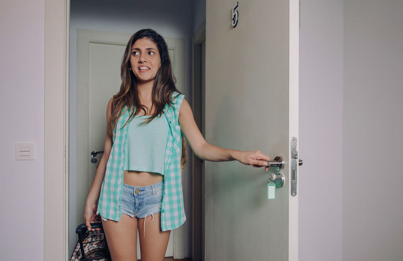 Young Woman Opening Door At Home