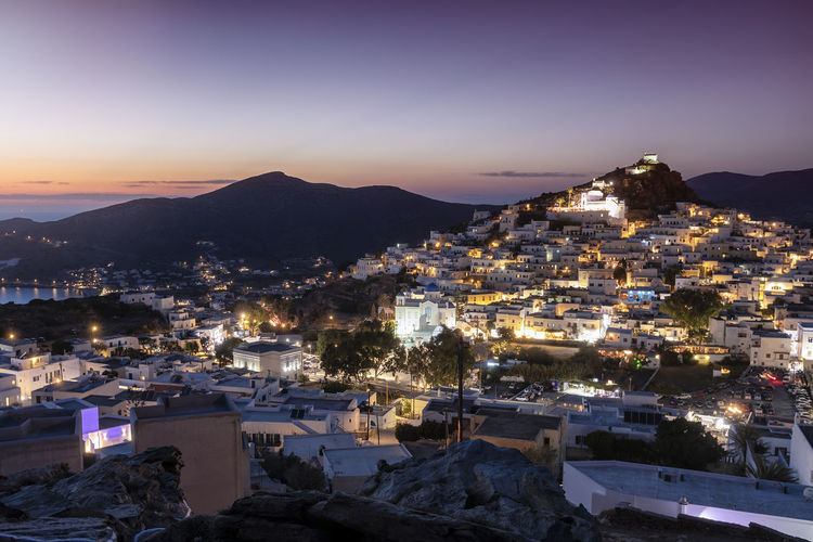 View to the illuminated town Chora of Ios island on the Cyclades of Greece after summer sunset Architecture Cityscape Mountain Sky Residential District Sunset High Angle View Illuminated Dusk Town TOWNSCAPE Greece Ios Cyclades Summer Island Evening Lights Chora Travel Destinations Tourist Attraction  Greek Mediterranean  Europe Aegean Sea