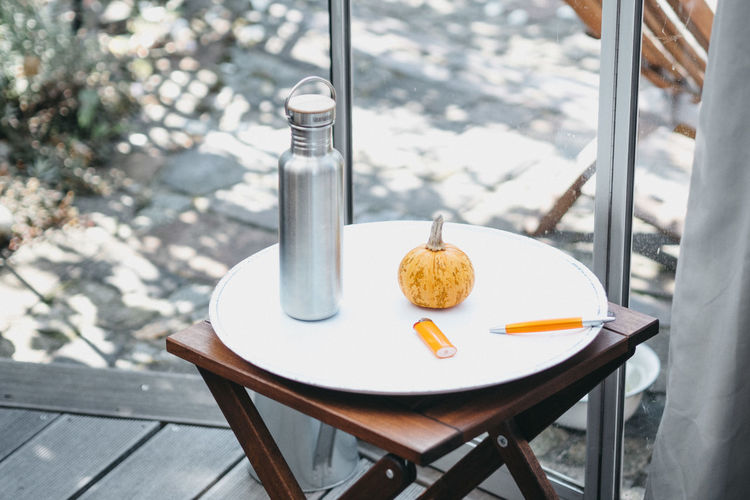 High Angle View Of Insulated Drink Container By Pumpkin On Stool At Floorboard