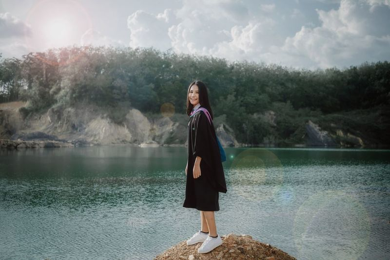Smiling young woman standing by lake against mountain