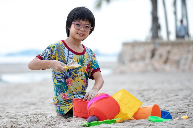 Portrait Asian girl with eyeglasses builds the sand castle on the beach by colourful models Childhood Real People Child Leisure Activity One Person Land Front View Beach Lifestyles Casual Clothing Focus On Foreground Girls Day Sand Females Nature Toy Outdoors Innocence Castle Builing Model