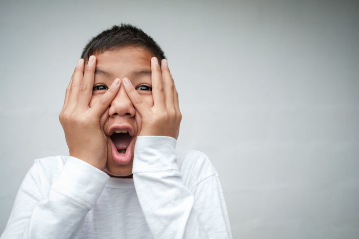 Child Childhood Children Only Disbelief Front View Gray Gray Background Head In Hands Headshot Human Body Part Human Face Human Mouth Looking At Camera Making A Face Males  Mouth Open One Boy Only One Person People Portrait Screaming Shock Shouting Studio Shot Surprise