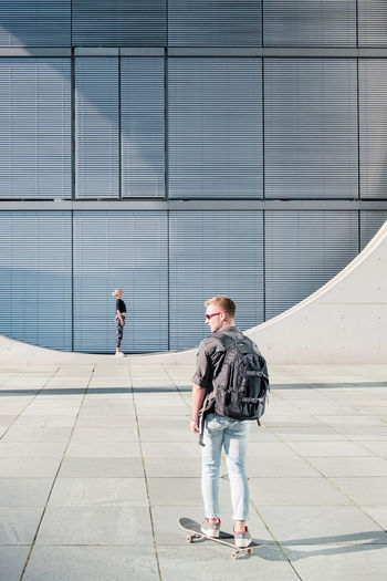 Adult Architecture Building Building Exterior Built Structure Casual Clothing City Day Footpath Full Length Office Building Exterior Outdoors People Real People Standing Sunlight Two People Walking Women Young Adult