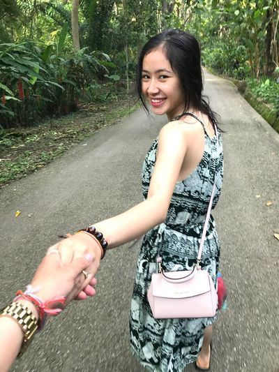 Portrait of smiling young woman holding hands of friend while walking on road
