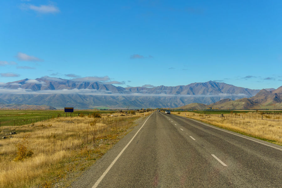Typical rural road in New Zealand, where the road often leads to mountain range in the distance with low hanging long clouds. Day Landscape Mountain Nature No People Outdoors Road Scenics Sky The Way Forward