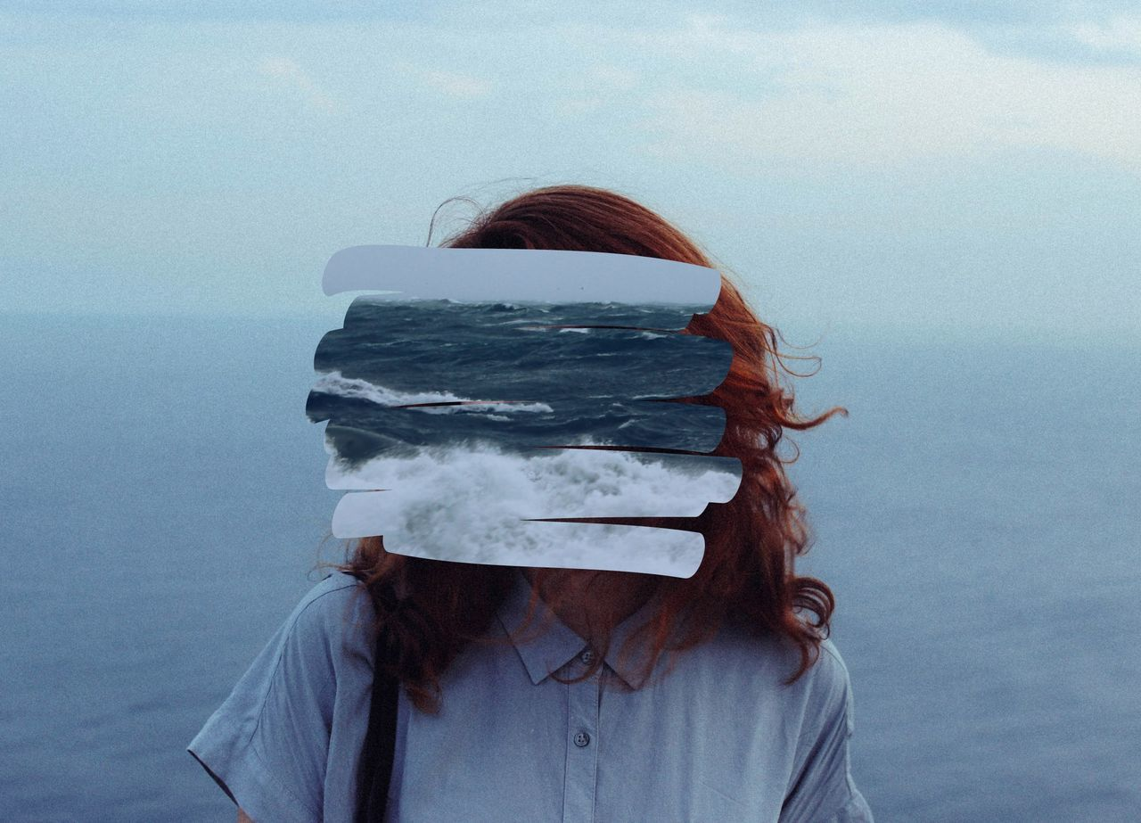 Woman's face obscured by sea