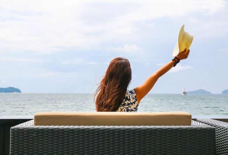 Rear view of woman holding hat while sitting by sea against sky