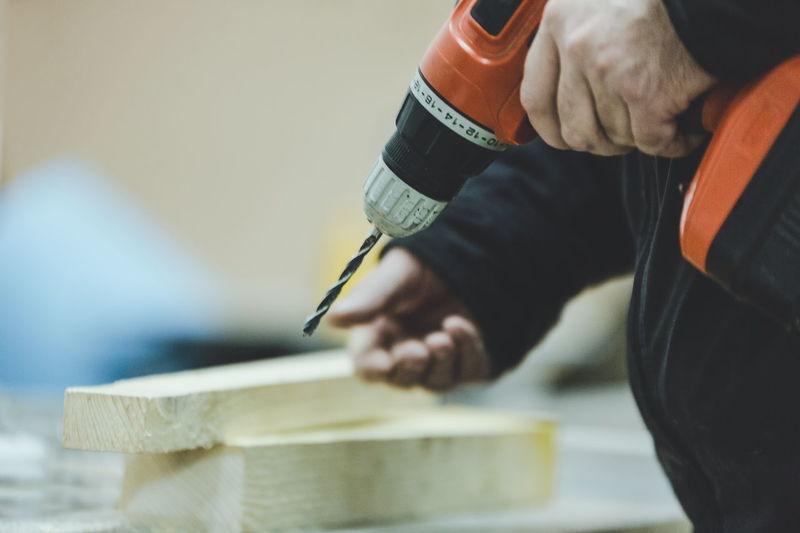 Close-up of man drilling wood