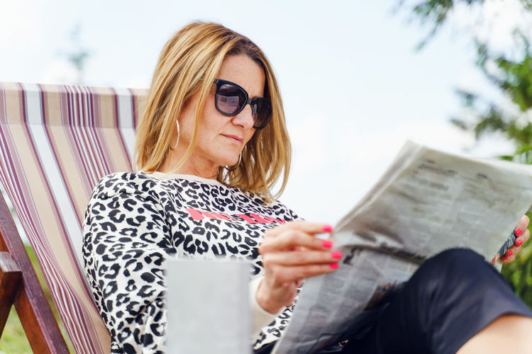 Mid adult woman wearing sunglasses while sitting outdoors