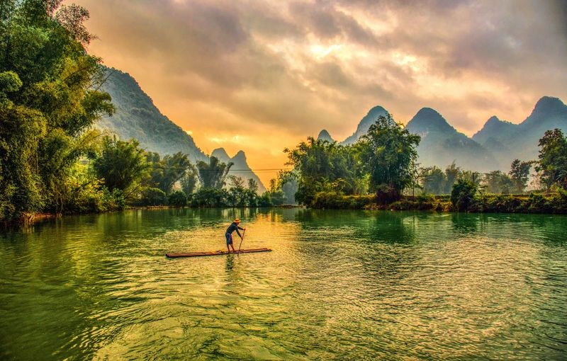 Man paddleboarding in lake against mountains during sunset