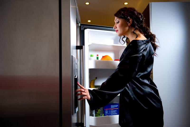 Sensuous woman wearing black bathrobe looking in refrigerator at home