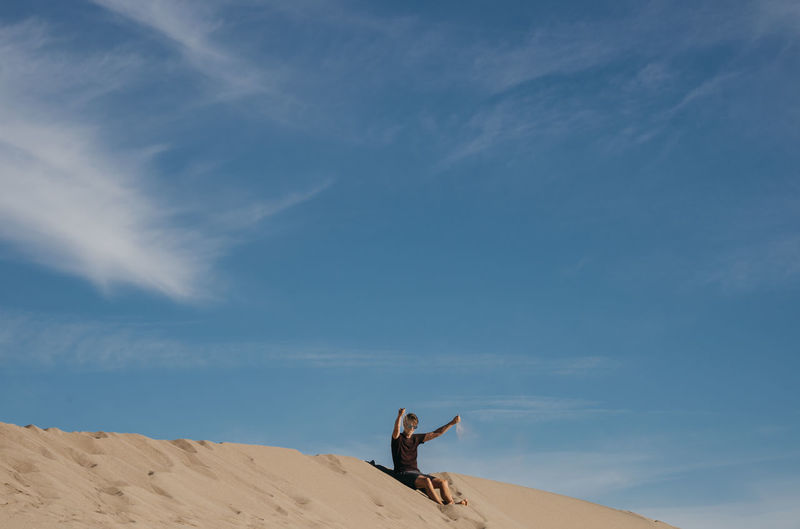 Man with arms raised on sand against sky