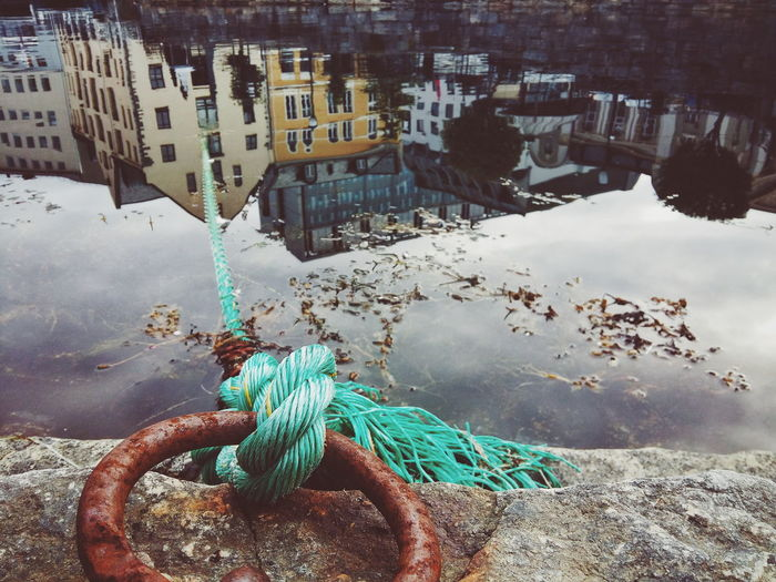 Rope tied on mooring ring with buildings reflecting in calm lake
