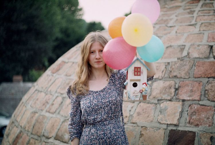 Film Architecture Balloon Beautiful Woman Blond Hair Day Film Photography Focus On Foreground Front View Helium Balloon Looking At Camera Medium-length Hair One Person One Young Woman Only Outdoors People Portrait Real People Smiling Standing Waist Up Young Adult Young Women