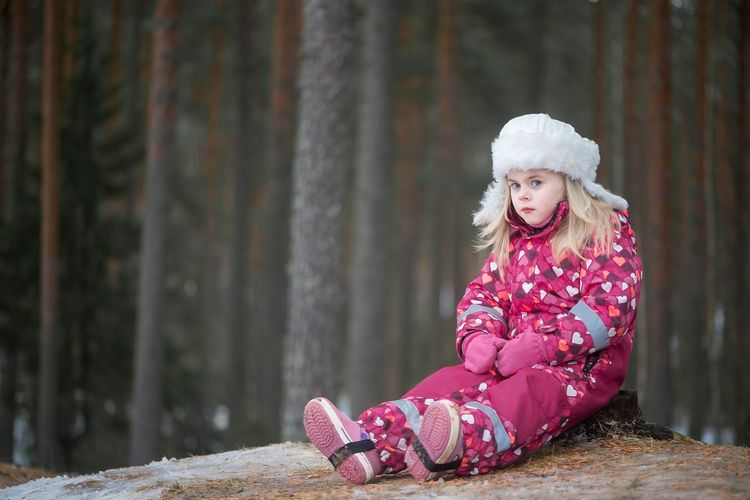 Portrait Of Girl In Warm Clothing Sitting By Trees In Forest During Winter