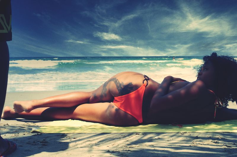 Young woman lying on shore against sky